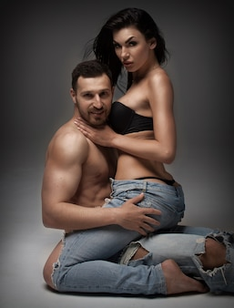 Casal jovem sexy. lindo casal sexy no fundo cinza, vestido em jeans azul.