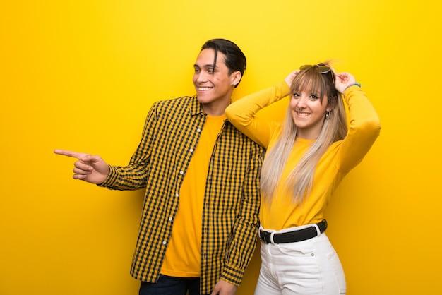 Casal jovem sobre fundo amarelo vibrante, apontando o dedo para o lado