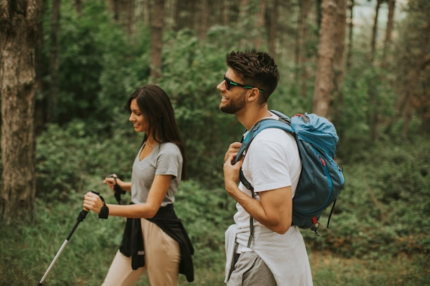 Casal jovem sorridente andando com mochilas na floresta