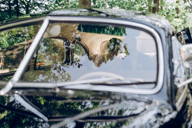 Casal jovem sorridente beijando enquanto está sentado em um carro