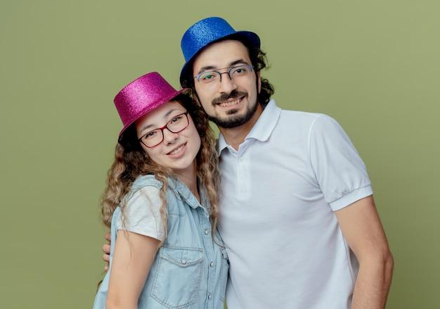 Casal jovem sorridente com chapéu rosa e azul isolado na parede verde oliva