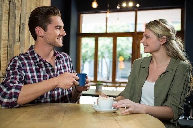 Casal jovem sorridente, conversando enquanto toma um café na mesa do refeitório