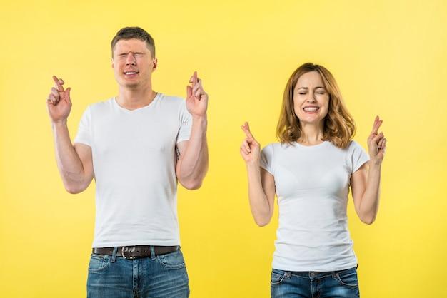 Casal jovem sorridente cruza os dedos em antecipação de algo agradável