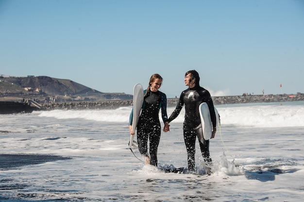 Casal jovem sorridente de surfistas em roupas de mergulho pretas, de mãos dadas e andando na água com pranchas de surf