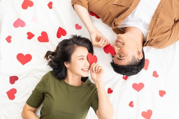 Casal jovem sorridente, deitado na cama com muitas formas de coração.
