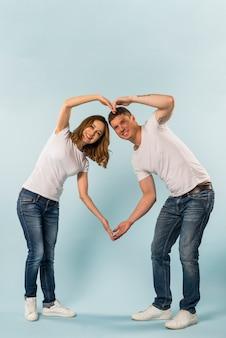 Casal jovem sorridente fazendo formato de coração com as mãos contra o fundo azul