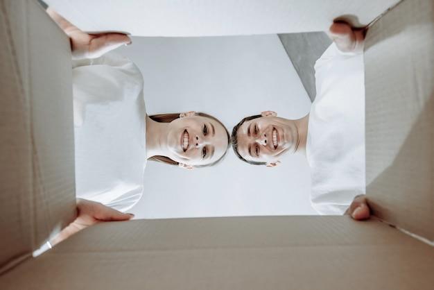 Casal jovem sorridente, homem e mulher, abrem a caixa de papelão e olham dentro da nova casa