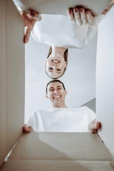 Casal jovem sorridente, homem e mulher, abrem a caixa de papelão e olham para dentro, na nova casa, conceito de mudança e descompactação