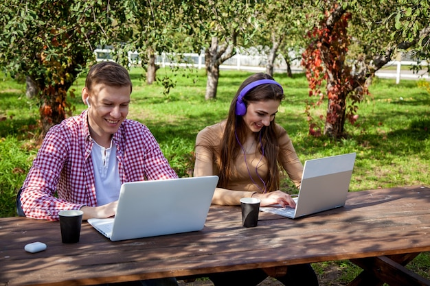 Casal jovem sorridente passa algum tempo juntos no parque, estuda e trabalha enquanto está sentado em uma mesa de madeira com um laptop. cara com uma garota com gadgets no parque