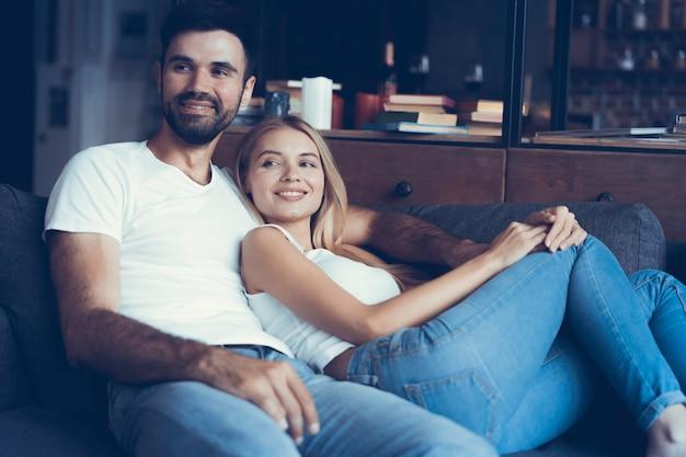 Casal jovem sorridente, relaxando e assistindo tv em casa.
