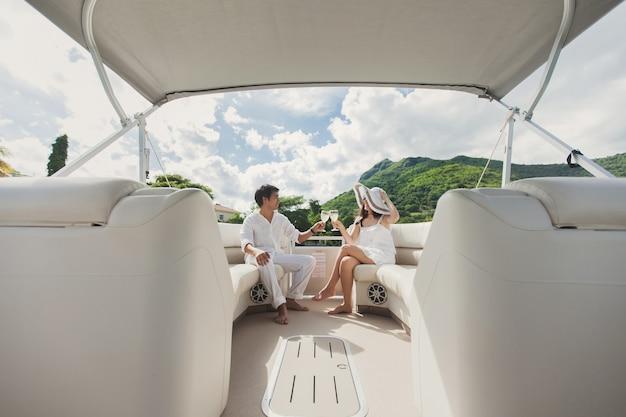 Casal jovem sorridente segurando taças com champanhe e olhando um para o outro enquanto está sentado a bordo do iate