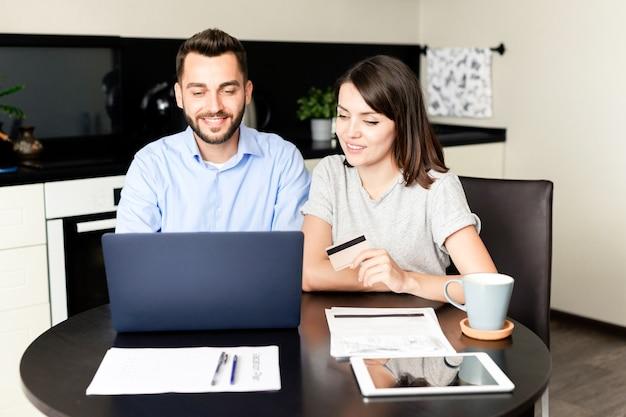 Casal jovem sorridente, sentado à mesa da cozinha, usando laptop e cartão de crédito para pagar contas online