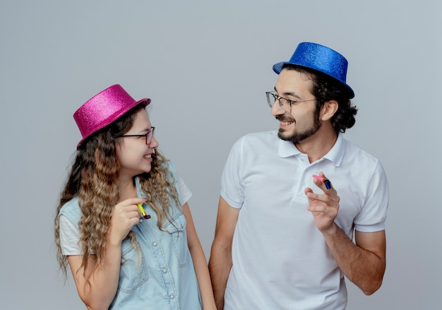 Casal jovem sorridente, usando chapéus cor de rosa e azul, olhando um para o outro segurando um apito