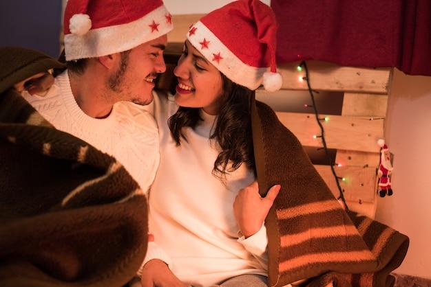 Casal jovem sorrindo e aproximando o rosto, usando chapéus de natal e agasalhos, enrolados em uma manta de inverno