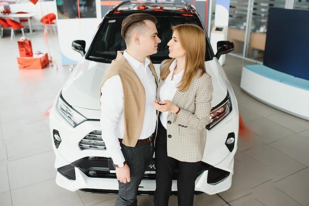 Casal jovem sorrindo para showroom de automóveis