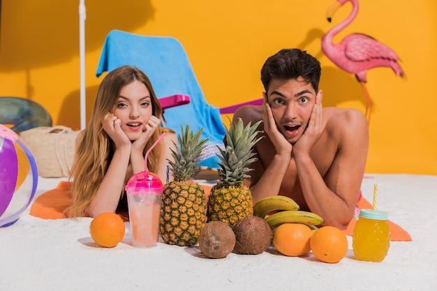 Casal jovem surpreso em beachwear descansando na areia no studio