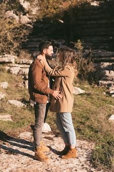 Casal jovem tiro completo abraçando na natureza