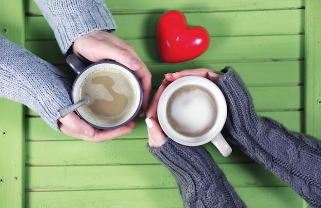 Casal jovem tomando café quente em uma mesa de madeira para um encontro