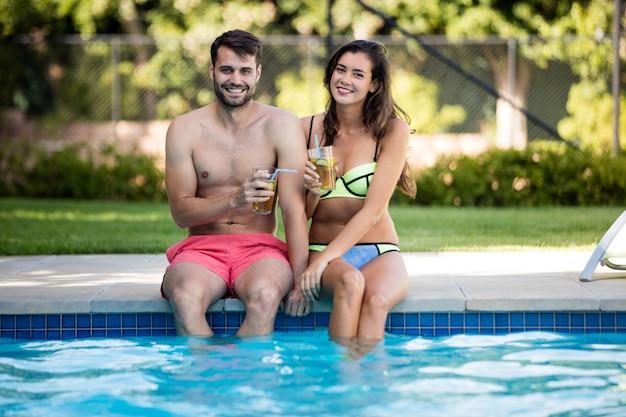 Casal jovem tomando chá gelado à beira da piscina em um dia ensolarado