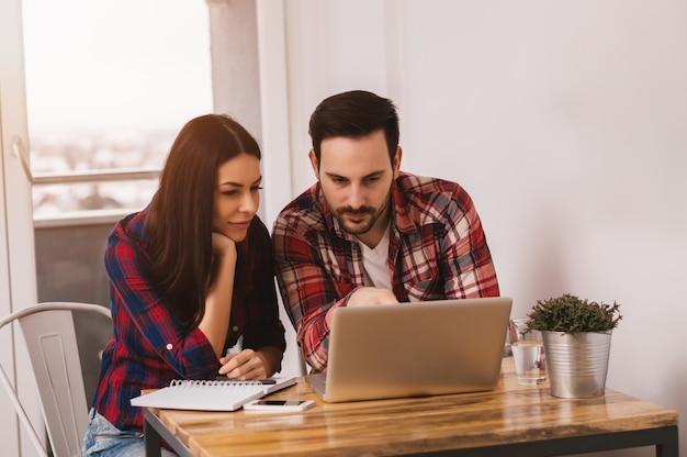 Casal jovem trabalhando juntos no laptop em casa
