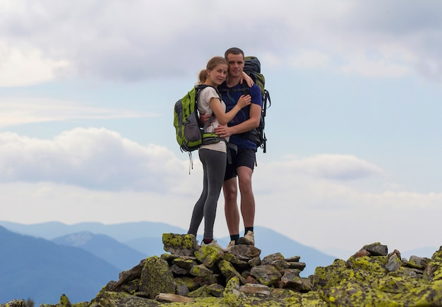 Casal jovem turista com mochilas, homem atlético e garota bonita em pé abraçado no topo da montanha rochosa no panorama da montanha nublada. conceito de turismo, viagens, escalada e amizade.