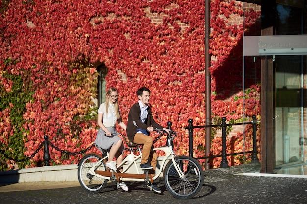 Casal jovem turista, homem bonito e mulher ciclismo bicicleta tandem no dia ensolarado ensolarado de outono no fundo da parede de tijolo totalmente coberto de folhas de hera vermelha.