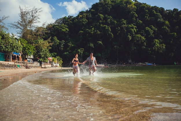 Casal jovem turista linda, de mãos dadas, correndo ao longo da praia