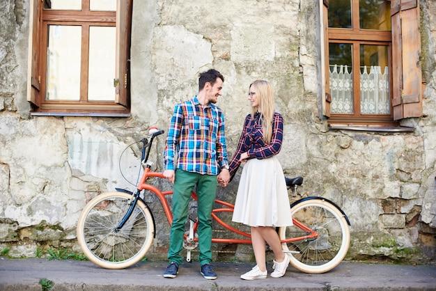Casal jovem turista romântico feliz, homem barbudo e mulher loira juntos, de mãos dadas e olhando para o outro em moderna bicicleta tandem na calçada vazia na calçada na parede rachada do edifício antigo