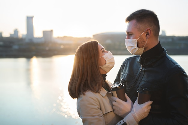 Casal jovem, um homem e uma mulher em máscaras e luvas médicas, tomam café em copos descartáveis na rua e olham um para o outro
