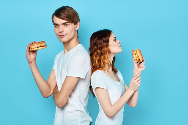 Casal jovem usando camiseta branca com hambúrgueres nas mãos lanche fast-food