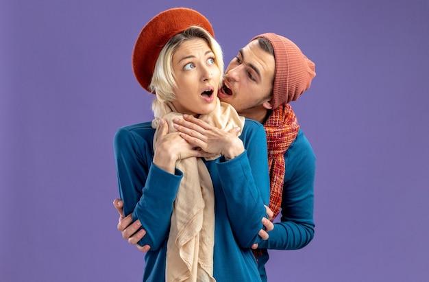 Casal jovem usando chapéu com lenço no dia dos namorados. garota assustada olhando o cara ao lado abraçou ela isolada sobre fundo azul
