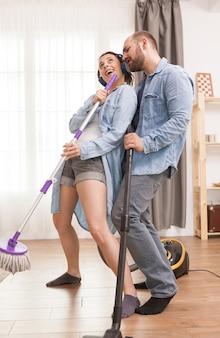 Casal jovem usando esfregão de limpeza como microfone