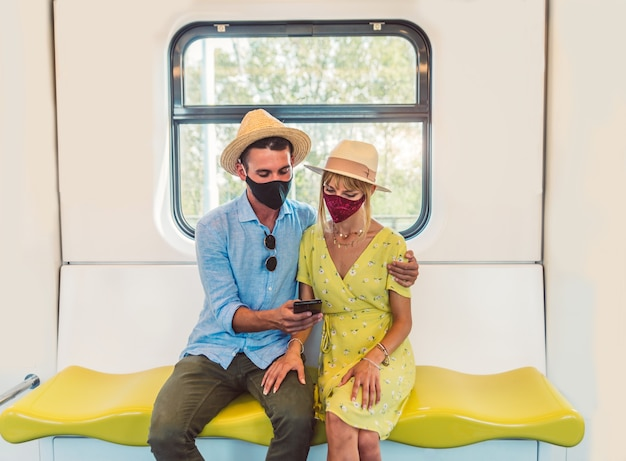 Casal jovem usando máscara facial usando telefone inteligente
