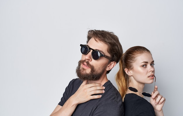 Casal jovem usando óculos escuros, moda casual, estúdio, romance