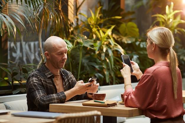 Casal jovem usando telefones celulares à mesa durante uma reunião no cyber café