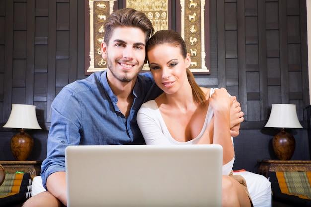 Casal jovem usando um computador portátil em um quarto de hotel asiático