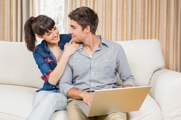 Casal jovem usando um laptop enquanto está sentado em um sofá na sala de estar