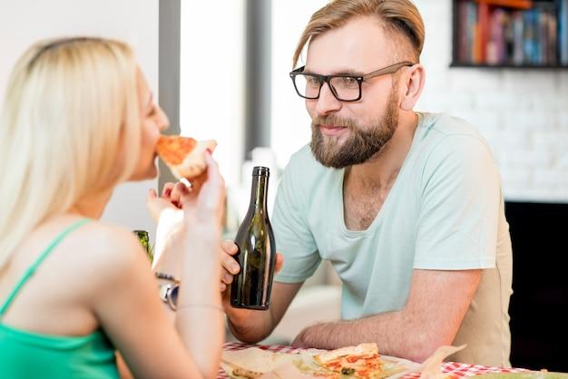 Casal jovem vestido de forma casual almoçando com pizza e cerveja em casa