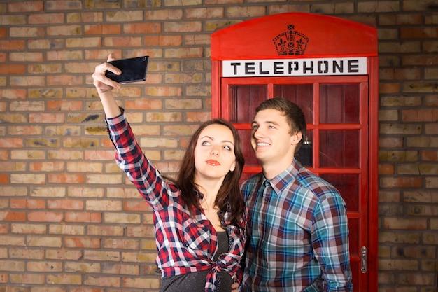 Casal jovem vestindo camisas xadrez fazendo um autorretrato com o celular na frente da cabine telefônica vermelha