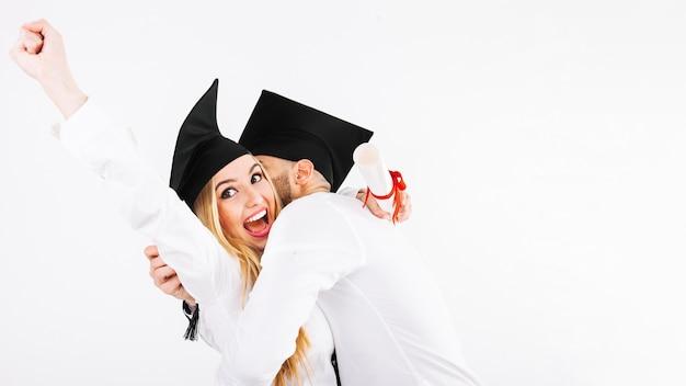 Casal jovial comemorando diplomas