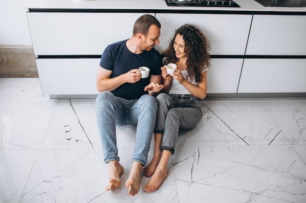Casal junto na cozinha tomando café