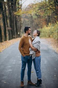 Casal junto no parque coberto no cobertor