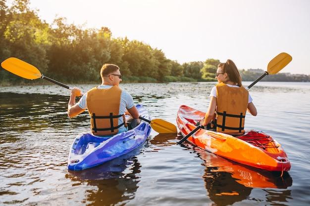 Casal juntos de caiaque no rio