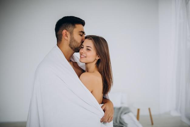 Casal juntos se abraçando sob um cobertor branco
