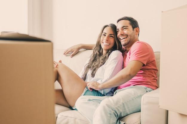 Casal latino alegre curtindo sua nova casa, relaxando no sofá entre caixas de papelão, olhando para longe e rindo