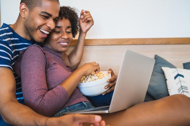 Casal latino assistindo um filme com o laptop em casa.