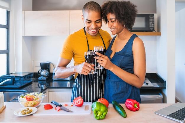 Casal latino cozinhando na cozinha.