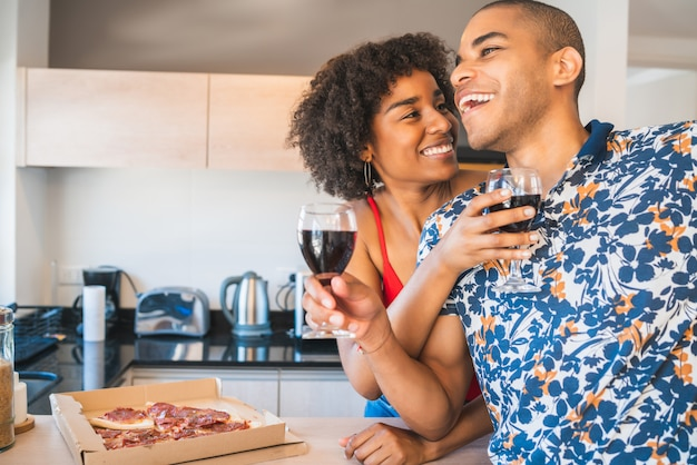 Casal latino feliz jantando em casa.