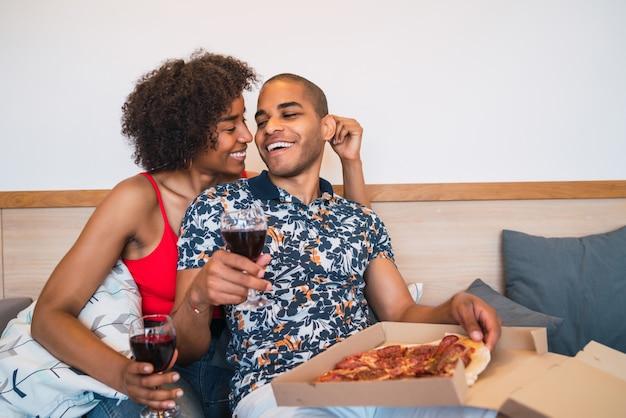 Casal latino feliz jantando juntos.