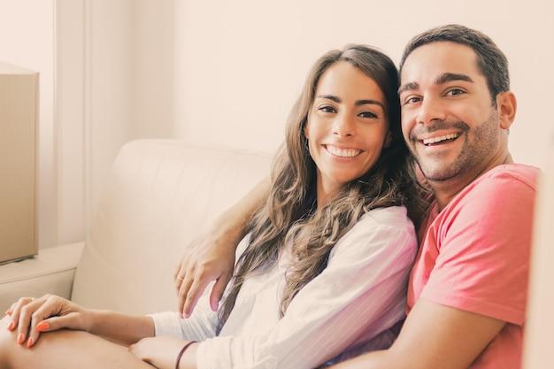 Casal latino feliz sentado no sofá entre caixas de papelão na casa nova
